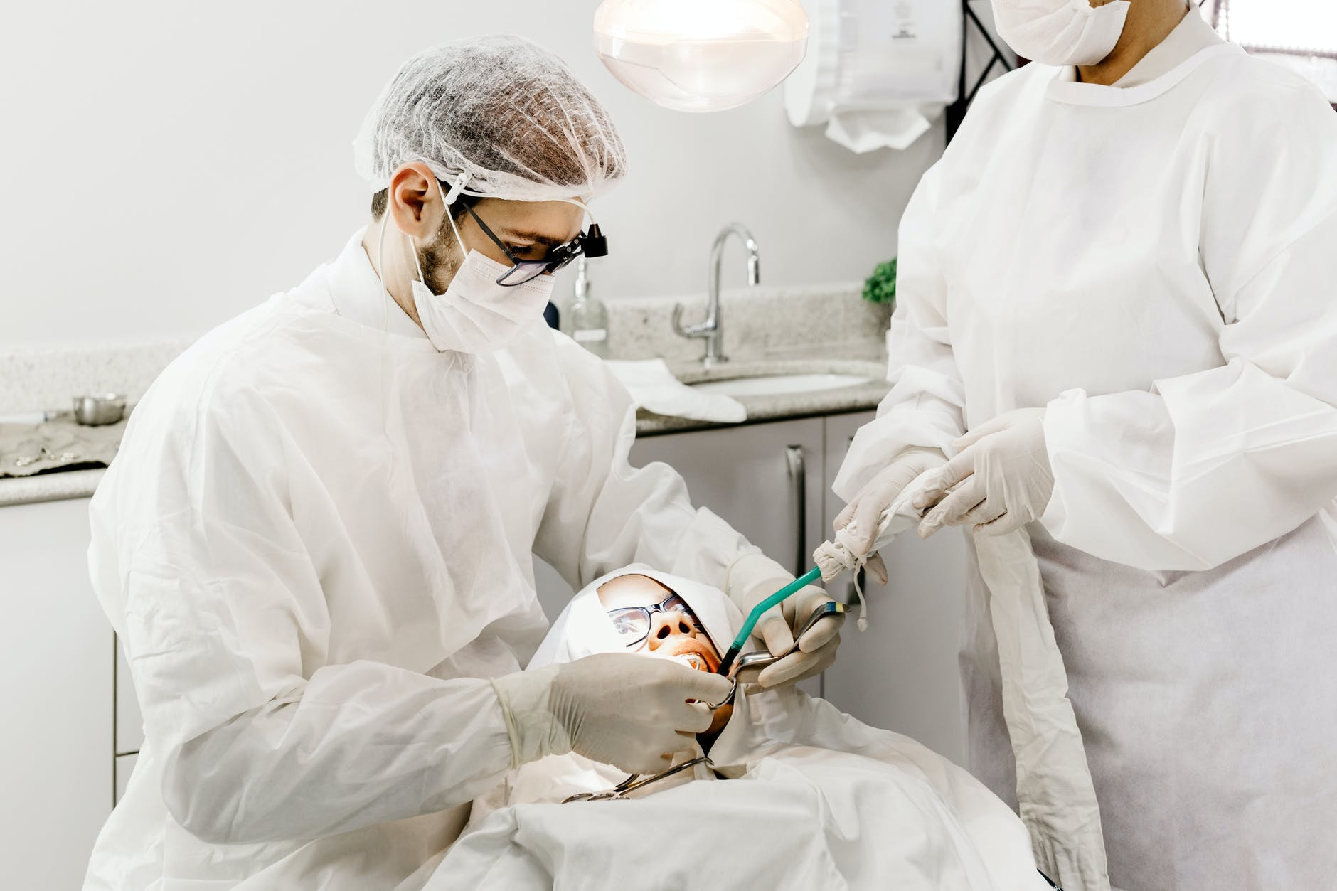 anonymous dentist with assistant treating teeth of patient